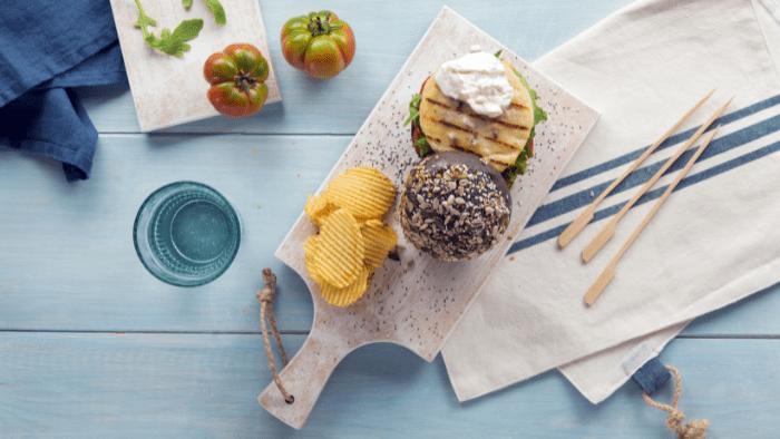 Burger di pesce con pane nero, rucola, stracciatella e pomodori